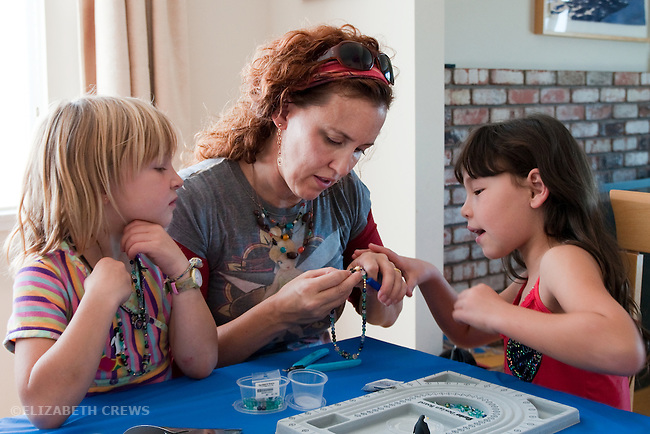 Berkeley CA Beading teacher helping girls, seven, make necklaces during birthday party  MR