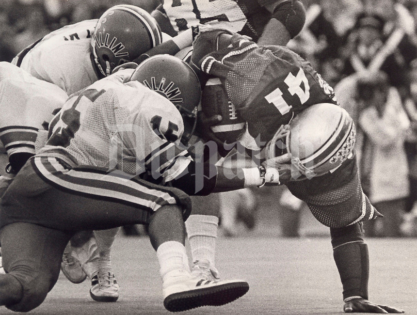 Illinois' John Ayres finds a way to drag down Ohio State's Keith Byars (41). 5:45, 3rd quarter 10-13-1984. Columbus Dispatch photo by Jeff Hinckley