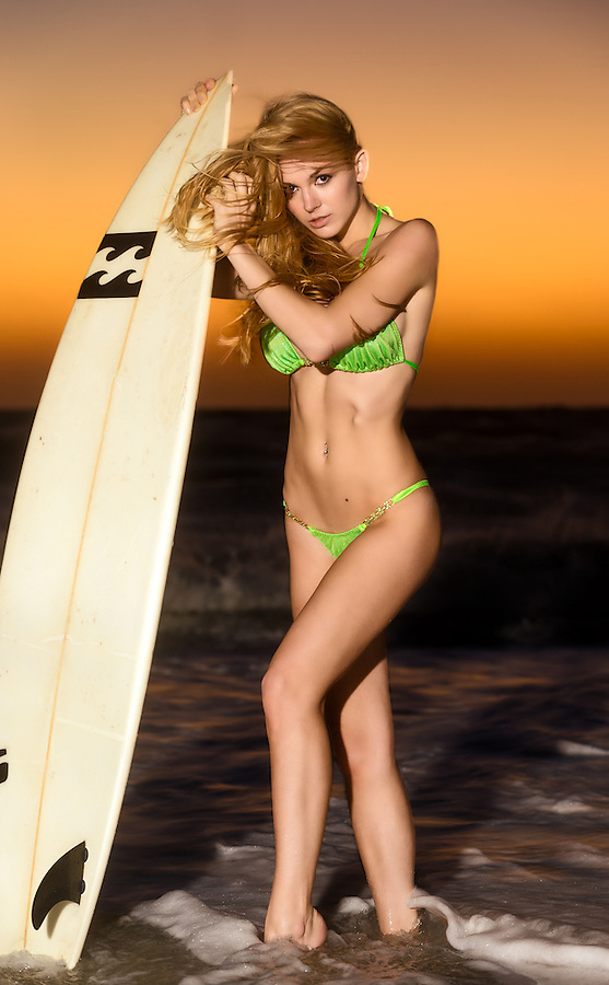 Sensual woman holding a surf table in the beach at dusk