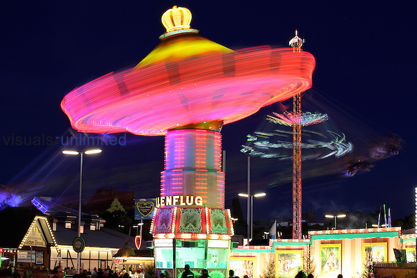 Oktoberfest, Munich, Germany 2011. Long exposure at night of Wellenflug chain carousel fairground ride with Starflyer 48 chain carousel tower behind.