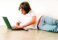 Teenage boy laying on floor using a laptop computer.