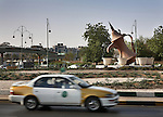 Taxi drives past a coffeepot roundabout in Al Ain city, United Arab Emirates