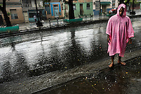 A Cuban man, wearing a pink raincoat, stands barefoot during a heavy rain on the street of Santiago de Cuba, Cuba, 1 August 2008. About 50 years after the national rebellion, led by Fidel Castro, and adopting the communist ideology shortly after the victory, the Caribbean island of Cuba is the only country in Americas having the communist political system. Although the Cuban state-controlled economy has never been developed enough to allow Cubans living in social conditions similar to the US or to Europe, mostly middle-age and older Cubans still support the Castro Brothers' regime and the idea of the Cuban Revolution. Since the 1990s Cuba struggles with chronic economic crisis and mainly young Cubans call for the economic changes.