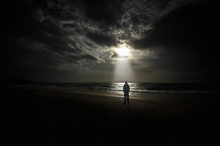 Conceptual beach scene with lone male figure and sunbeam