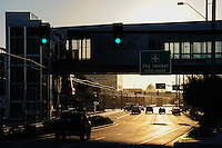 """Phoenix, Arizona. Eastbound traffic on Washington Street at 44th Street in Phoenix, Arizona. At left a portion of the """"44th Street and Washington Street"""" Light Rail station is seen below the bridge that connects people to the Sky Train that takes them to the International Sky Harbor Airport. The image was taken just after sunrise. Photo Eduardo Barraza © 2015"""