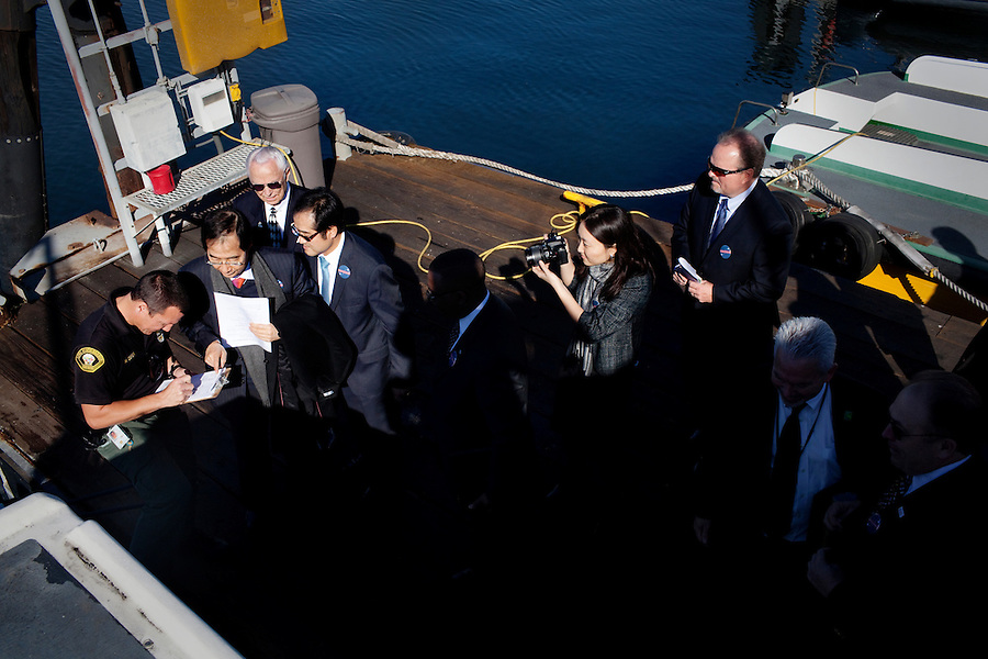 Long Beach, California, January 24, 2011 - Han Duk-soo, South Korea's Ambassador to the United States (second from left) giving his name to a security officer before boarding a boat during a tour of the Port of Long Beach along with Chamber of Commerce representatives, South Korean advisors and local businessmen. The delegation was in town as part of a sustained effort since 2007 to sell the idea of the U.S.-Korea Free Trade Agreement to the US. Final language is still being worked out, but the agreement could come to a vote in the next few weeks. ..The U.S.-Korea Free Trade Agreement would eliminate tariffs on 95% of U.S. goods within five years of its signing and could boost U.S. exports by $11 billion annually, the International Trade Commission estimates. It would also reduce trade restrictions and tariffs on U.S. auto and beef exports while continuing American tariffs on South Korean autos for a limited time. Southern California would almost certainly be a major beneficiary. Nearly $16 billion in goods moved between South Korean and Southland ports in 2009. The Los Angeles area is home to an estimated 600,000 Korean Americans, many of whom have strong business ties to their homeland and are heavily invested in the local economy. Southern California's entertainment industry also supports the pact, which would clamp down on unauthorized copying and sharing of music and videos in South Korea, where piracy is a serious problem..