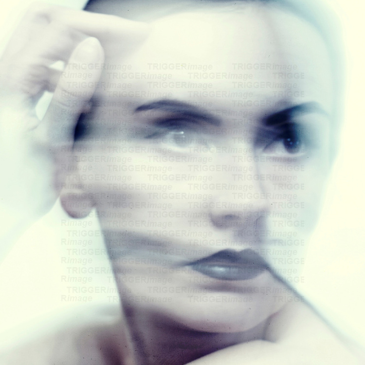 Close up of womans face with black lips with reflection in cold tone with hand near face