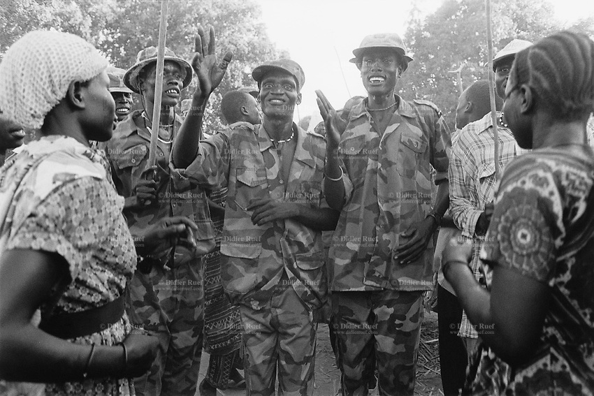 Sudan. Southern part. Bahr El Ghazal. Akoc. Dinka tribe area. A celebration to welcome the soldiers of the Sudan People's Liberation Army (SPLA). The men are dressed in military outfits. © 1998 Didier Ruef