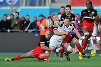 Chris Cook of Bath Rugby offloads the ball after being double-tackled by Charlie Hodgson and Jackson Wray. Aviva Premiership match, between Saracens and Bath Rugby on January 30, 2016 at Allianz Park in London, England. Photo by: Patrick Khachfe / Onside Images