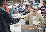 """Maria Natividad Granados, a Methodist woman in Nuevo Laredo, Mexico, serves food to Cuban immigrants in that city's Plaza Benito Juarez on March 3, 2017. Hundreds of Cubans are stuck in the border city, caught in limbo by the elimination in January of the infamous """"wet foot, dry foot"""" policy of the United States. They are not allowed to enter the U.S. yet don't want to return to Cuba. Many of the city's churches have become temporary shelters for the immigrants, and congregations rotate responsibility for feeding the Cubans, who have slowly been forced to appreciate Mexican cuisine. Such solidarity from ordinary Mexicans is being tested these days, as not only are the Cubans stuck at the border, but the U.S. has stepped up deportations of Mexican nationals, while at the same time detaining many undocumented workers from other nations and simply dumping them on the US-Mexico border. Granados is a member of the El Ebenezer Methodist Church in Nuevo Laredo."""