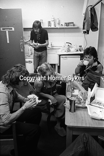 Paul and Linda McCartney Wings Tour 1975. Paul, Linda and Denny Laine tuck into a fast food take away fish and chips meal,  Elstree rehearsal studio London,  England.