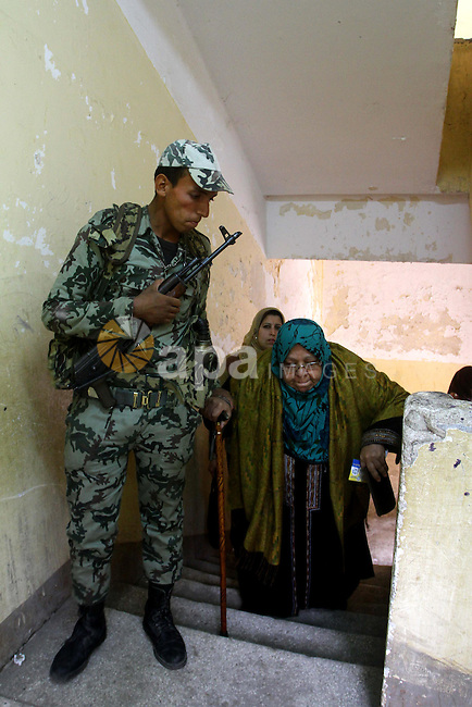 Army soldier helps an Egyptian woman to cast her ballot at a parliamentary polling station in Cairo on November 29, 2011. Egypt hailed the start of its first post-revolution election as a triumph for democracy as more voters headed to the polls, boosting turn-out for a vote that had looked in doubt last week. Photo by Ashraf Amra