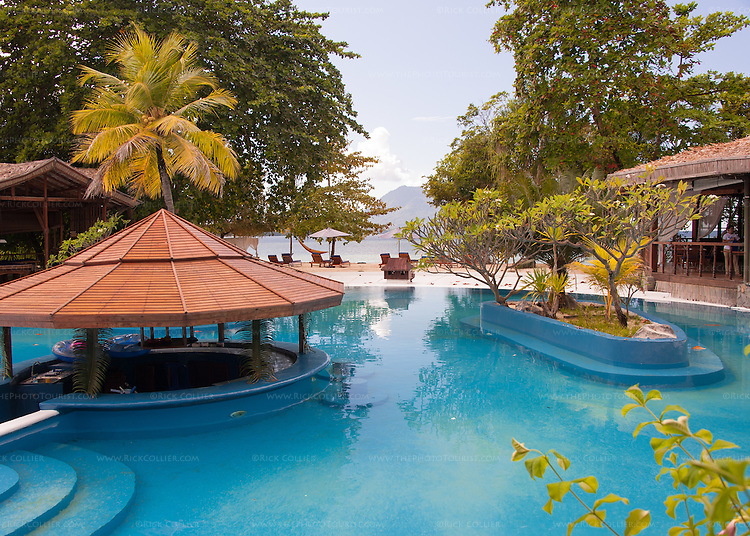 A beautiful blue pool separates the restaurant from bar and reception areas at the Siladen Resort and Spa, on Siladen Island, off North Sulawesi, Indonesia.  (The volcano island Manado Tua is visible in the distance beyond the beach.)