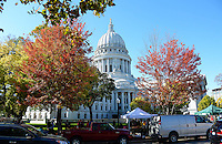The Wisconsin State Capitol Building is seen through the autumn trees on the Capitol Square during the Dane County Farmers' Market on Saturday, October 17, 2015 in Madison, Wisconsin