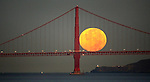 The full moon set seemingly on the deck of the Golden Gate Bridge in San Francisco, California.
