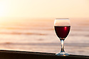 Glass of red wine on deck railing of house on the beach at Yachats on the central Oregon coast.