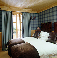 The headboards of the twin beds in this guest bedroom are upholstered in suede and decorated with antique bronze studs and the walls are covered in a blue plaid