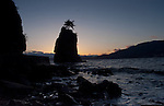 Rock jutting out of the sea silhouetted against the sky and cliffs.Stanley park, Vancouver,British Colombia, Canada.