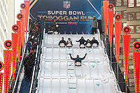 Football fans slide down the 180 foot long, four story high toboggan run on opening day of Super Bowl Boulevard in Midtown Manhattan in New York on Wednesday, January 29, 2014. Despite the game being held in New Jersey on February 2 sports fans are expected to pack New York to take part in the multitude of activities planned around the game including the 13 block stretch of Broadway, running from 34th street through 47th street that will host Super Bowl Blvd. from January 29 to February 1. (© Richard B. Levine)