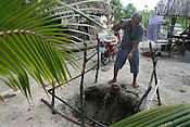 Kiriata Riteti, from Buota village, on the South Pacific island of Kiribati, tests the water from his well on his land. The water has recently become brackish and salty in taste, and unusable, due to the rising sea water levels, and the encroachment of sea water onto his property.