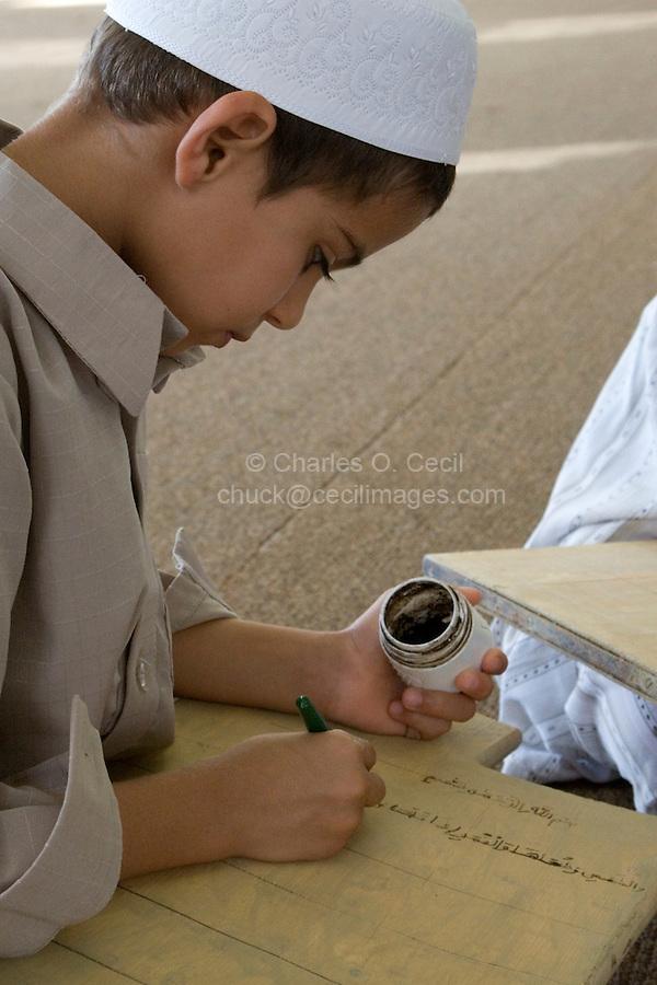 Zliten, Libya. Boy Writes Verses from the Koran on his Prayer Board in the Madrasa of Sidi Abdusalaam.  He wears the traditional hat, a tagiyah.