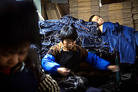 Textile workers sewing jeans while a young child sleeps nearby at a garment factory. The factory, which specifically carries out a wear-and-tear process used to achieve a fashionable distressed look, produces approximately 10,000 pairs of jeans every day. Thousands of workers labour through the night scrubbing, spraying and tearing jeans in order to meet the production demand. The factory is owned by Huang Dehong, who left his impoverished village and arrived penniless in Zhongshan twenty years ago. China, the &quot;factory of the world&quot;, is now one of the world's largest producers of jeans and its textile workers are among the 200 million migrant labourers criss-crossing the country looking for a better life.