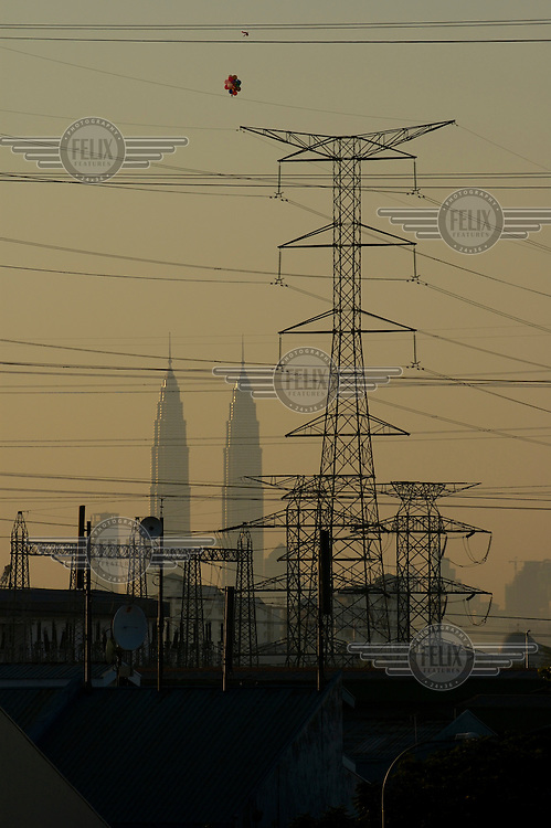 View from the edge of the city showing electricity pylons and the Petronas Twin Towers rising behind.