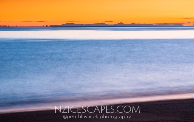 Orange sunrise on pristine and empty beach in Totaranui on Abel Tasman Coastal Track, Abel Tasman National Park, Nelson Region, South Island, New Zealand