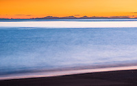 Orange sunrise on pristine and empty beach in Totaranui on Abel Tasman Coastal Track, Abel Tasman National Park, Nelson Region, South Island, New Zealand