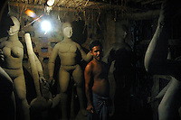 INDIA (West Bengal - Calcutta)  2006, An idol maker in his studio at Kumortuli. Kumortuli in North Calcutta is the hub of Durga idol makers. During the other time of the year the artists engage themselves in prepairing other idols and masks depending on the assignments. But the most of the earning they aquire from making Durga idols. A Durga idol can cost up to 7000 usd. Which is a big price in Indian Currency.  Durga Puja Festival is the biggest festival among bengalies.  As Calcutta is the capital of West Bengal and cultural hub of  the bengali community Durga puja is held with the maximum pomp and vigour. Ritualistic worship, food, drink, new clothes, visiting friends and relatives places and merryment is a part of it. In this festival the hindus worship a ten handed godess riding on a lion armed wth all possible deadly ancient weapons along with her 4 children (Ganesha - God for sucess, Saraswati - Goddess for arts and education, Laxmi - Goddess of wealth and prosperity, Kartikeya - The god of manly hood and beauty). Durga is symbolised as the women power in Indian Mythology.  In Calcutta people from all the religions enjoy these four days of festival in the moth of October. Now the religious festival has become the biggest cultural extravagenza of Calcutta the cultural capital of India. Artistry and craftsmanship can be seen in different sizes and shapes in form of the idol, the interior decor and as well as the pandals erected on the streets, roads and  parks.- Arindam Mukherjee