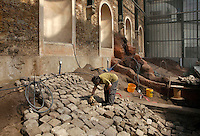 New Caledonia Glasshouse (formerly The Mexican Hothouse), 1830s, Charles Rohault de Fleury, Jardin des Plantes, Museum National d'Histoire Naturelle, Paris, France. General view of a worker putting old paving stones into position. They will be covered with soil to form a drainage system. The New Caledonia Glasshouse, or Hothouse, was the first French glass and iron building.