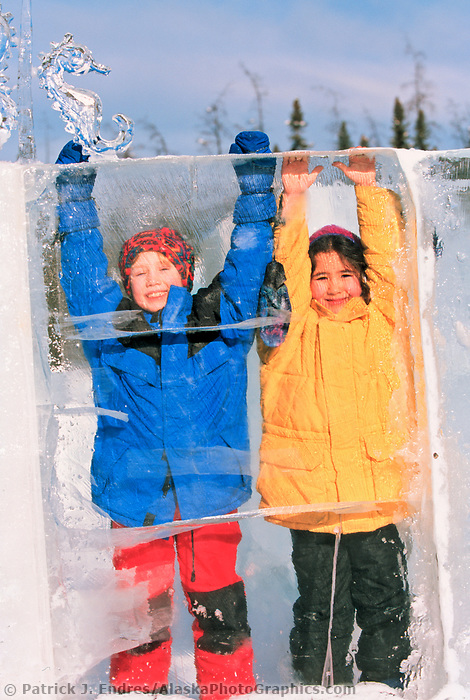 Kids play along the wall of a maze constructed out of panels of ice at the Ice Park, in Fairbanks, Alaska.