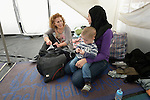 Despina Katsivelaki (left), the program coordinator for International Orthodox Christian Charities in Greece, talks with a refugee woman and her child inside a tent in a city park on the Greek island of Chios. The park is full of tents sheltering refugees who crossed the Aegean Sea in small boats from Turkey. They were registered and provided with food and shelter in a reception center built with support from IOCC, a member of the ACT Alliance. Many of them then move to the city park where they await a ferry to take them to Athens and then on toward western Europe. Hundreds of thousands of refugees and migrants have passed through Greece in 2015.