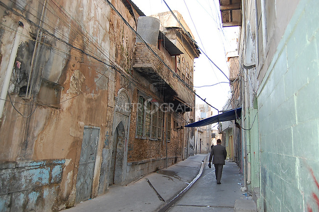 IRAQ, MOSUL:  A man walks by traditional wooden houses in the old city of Mosul....Photo by Hakar Said/Metrography