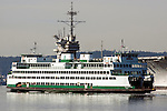 The Washington State Ferry, Kaleetam, passes the USS Ranger as it's towed from Puget Sound Naval Shipyard's Inactive Ship Maintenance Facility in Bremerton, WA. on March 5, 2015. The carrier is en route to scraped at International Shipbreaking in Texas.The aircraft carrier was active from 1957 to 1993, when it entered the mothball fleet. The Navy announced a deal Dec. 22 to pay a penny and the value of the ship's scrap metal to take it away. It must make a five-month, 16,000-mile trip around South America because it can't fit through the Panama Canal.  ©2015. Jim Bryant Photo. All RIGHTS RESERVED.