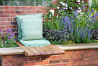 Garden bench and pillows with raised flower border with herbs Salvia officinalis, brick wall
