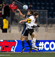 Patrick Mullins (15) of Maryland goes up for a header with Zach Carroll (2) during the NCAA Men's College Cup semifinals at PPL Park in Chester, PA.  Maryland defeated Virginia, 2-1.