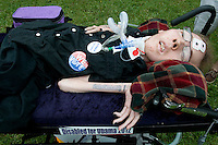 """TAMPA, FL - August 26, 2012 - Michael Phillips, 31, lays on a gurney. He had a sign propped on him that said """"I am voting for President Obama because...  I support a president who believes people with disabilities should live in communities."""" Phillips suffers from the disease Spinal muscular atrophy (SMA). He came to the Republican convention area with his mother and brother."""