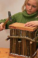Kinder bauen Vogel-Nistkasten für Meisen, Vogelnistkasten, Nistkasten, Kind nagelt ein Brett als Dach auf den Nistkasten aus Holzstäben