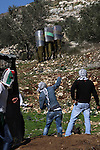 Palestinians throw stones to Israeli soldiers on the sidelines of a demonstration against the expropriations by Israel in the West Bank village of Kafr Qaddum, near Nablus, on November 30, 2012. Photo by Nedal Eshtayah