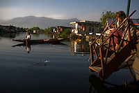 A tourist relaxes while fishing on the porch of Yellow Submarine, a house boat while a Kashmiri man paddles on Dal lake. Travel photographs of Srinagar, Kashmir, Jammu & Kashmir, India on 9th June 2009.  Photo by Suzanne Lee /  For The National