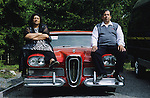 Kai and Katinka Palm, musicians of the group Romales, sitting on the bonnet of their vintage American Edsel. Tempere, Finland 2005