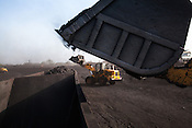 Employees of BCCL load up coal on a train carriage in Jharia, Jharkhand, India.