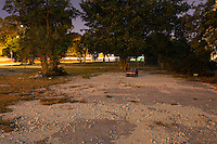 An abandoned toy car sits in a vacant lot at night.