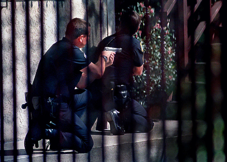 With guns drawn, West Los Angeles police officers surround an apartment building where a car theft suspect was hiding near Pico Blvd. and Bundy Drive in West L.A. STAFF PHOTO BY RICHARD HARTOG