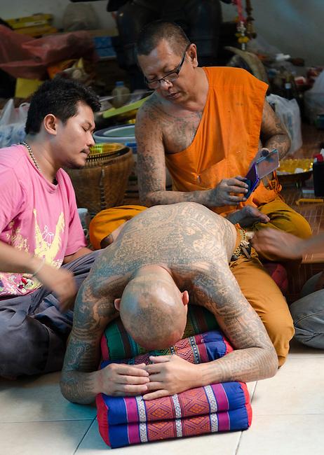Nakorn Chai Sri, Thailand, March 2, 2012, Wat Bang Phra Buddhist Monk prepares to stamp a sak yant magical tattoo pattern on a devotee in preparation.