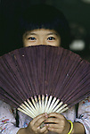 A curious girl hides from behind a hand fan in Hanoi, North Vietnam.  (Jim Bryant Photo)......