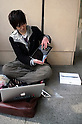 March 16, 2012, Tokyo, Japan - A young man checks his new iPad in the street. .Fans lined up overnight outside the Apple store in Ginza, to buy the new iPad. Japan was one of the first countries where Apple fans could get their hands on the new iPad.