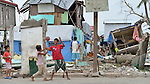 Boys play basketball amid the ruined houses of Tacloban, a city in the Philippines province of Leyte that was hit hard by Typhoon Haiyan in November 2013. The storm was known locally as Yolanda. The ACT Alliance has been active here and in affected communities throughout the region helping survivors to rebuild their homes and recover their livelihoods.