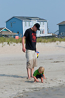 A 2 year old boy picks up shells on Carolina Beach with his father.